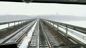 Train moves on the bridge across the river. Traveling by train in winter. Prospect of the railroad stock video footage