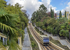 The train moves on rails on the mountain. The car moves on rails uphill Stock Image