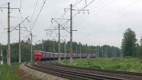 Train Moves Towards On Railroad Turn. Suburban electric train moves towards on railroad turn against skyline stock footage