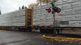 Train moves through town crossing. Corvallis, Oregon, Nov 11, 2015:Freight train moves through a town crossing. Train whistles and crossing bells heard stock footage