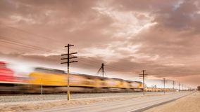 Train moves on tracks along a road with motion blurr stock photo