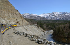 Train is moving along mountains Stock Photo