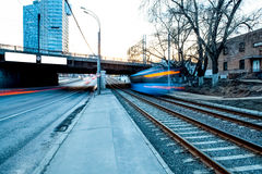 Train moving along platform in twilight. The night railroad in lamps and lights Stock Image