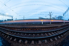 Train moving along platform in twilight. The night railroad in lamps and lights Stock Images