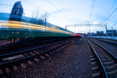 Train moving along platform in twilight. The night railroad in lamps and lights Stock Photos