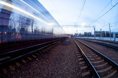 Train moving along platform in twilight. The night railroad in lamps and lights Royalty Free Stock Image