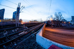 Train moving along platform in twilight. The night railroad in lamps and lights Royalty Free Stock Photography