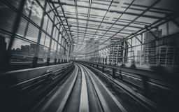 Train moving on city rail with motion blur. Front view of train moving in city rail tunnel with moderate motion blur in black and white filter. Transportation royalty free stock photos