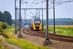 Train moving into distance. Dutch doubledecker train moving into the distance on double tracks in rural area Royalty Free Stock Image