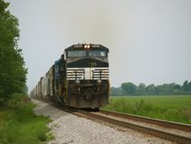 Train moving down the Tracks. Freight train moving down the tracks on an overcast summer day royalty free stock photo