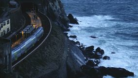 Train moving on Manarola station, slow-motion of waves breaking on rocky cliff. Stock footage stock footage