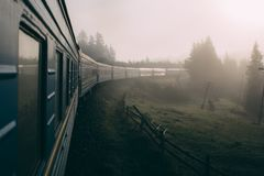 Train moving in the mountains in fog. Carpathian mountains. View from window stock photography