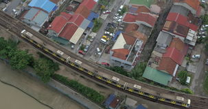Train moving on overground railway in Kuala Lumpur, Malaysia. High angle shot of train riding across the city along overground railroad in district with private stock video