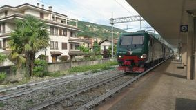 Train near a platform. 20.06.2016 - Stresa, Italy. Train near a platform Railway town buildings and nature stock video footage