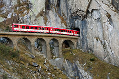Train on an old bridge is going into a tunnel Royalty Free Stock Image