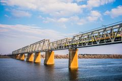 train over river bridge in sunny weather stock photography