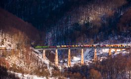 Train over viaduct in winter mountains. Lovely transportation scenery with snowy forested hills Stock Images