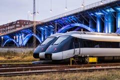 Train Paring under lit bridge Stock Photography