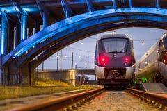 Train Paring under lit bridge Royalty Free Stock Images