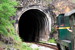 Train with pasengers going to the tunnel in the mountain.  stock images