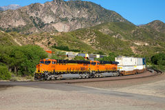 The train passes through the foothills. A goods train pulled away round the foot of a mountain Royalty Free Stock Images