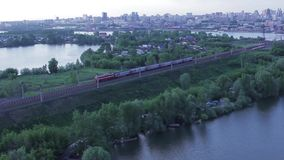 Train passes through the forest against the backdrop of the city, top view stock video footage