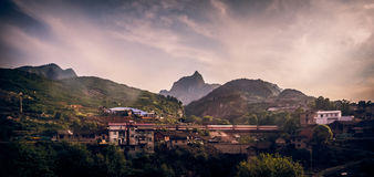 Train passes through mountain village in China. Royalty Free Stock Photos