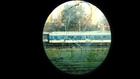 Train Passes through an Oval Window of an Old Wagon. A train passes through an Oval Window stock video footage