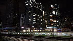 Train Passes over Bridge in Central Tokyo Japan at Night stock video footage