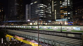 Train Passes over Bridge in Central Tokyo Japan at Night stock video