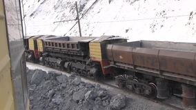 The train passes through the quarry. View from the window of the excavator on the empty cars of the electric train stock footage