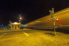 train passes at railroad crossing in the night at Route 66 Royalty Free Stock Images