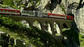The train passes through the viaduct. Place near the Devil`s bridge. Andermatt, Switzerland. Summer time stock video