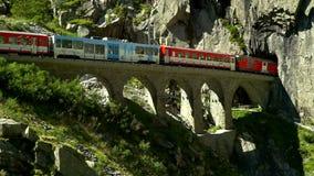 The train passes through the viaduct. Place near the Devil`s bridge. Andermatt, Switzerland. Summer time stock video footage