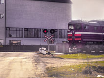Train passing across a level crossing on the road Royalty Free Stock Photos