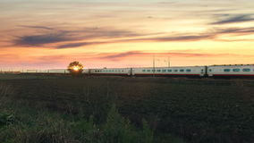 Train is passing against the sunset. Electric white and red passenger high speed train is passing in an empty land against a beautiful sunset stock video