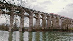 Train passing aqueduct. A train drives over a aqueduct over a river in Germany stock footage