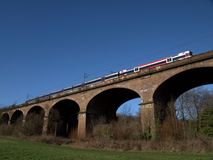 Train passing on an arched viaduct with blue sky Hanwell London UK Stock Images