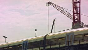 Train passing, crane in the background stock video footage