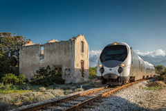 Train passing derelict station at Lumio in Corsica Stock Photos