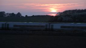 Train passing the fields during beautiful sunset stock video footage