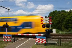Small bicycle level crossing with train passing by on high speed royalty free stock image