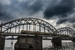Rail bridge over Daugava River Latvia. Train is passing over a iron and iconic bridge over Daugava River during a cold winter day. Clouds are heavy of rain and royalty free stock photo