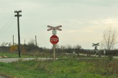 Train passing sign. Train passing by a railway-crossing with stop sign Stock Photos