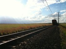 Train passing by on railway in nature setting. Electric train on railroad in a natural environment Stock Photography