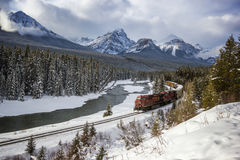 Train passing through river valley under the surveillance of mighty winter and snowy Rocky Mountains, Morants curve, Banff nationa Royalty Free Stock Photos