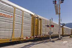 Train passing road crossing with signals Royalty Free Stock Photos