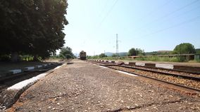 Train passing through a small railway station. Train passing through a small bulgarian railway station stock video footage