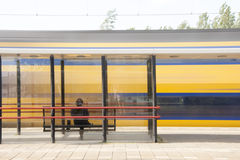 Train passing by a station Stock Photos