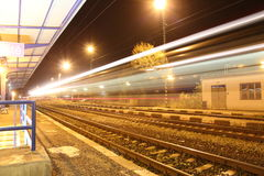Train passing station at night Stock Images